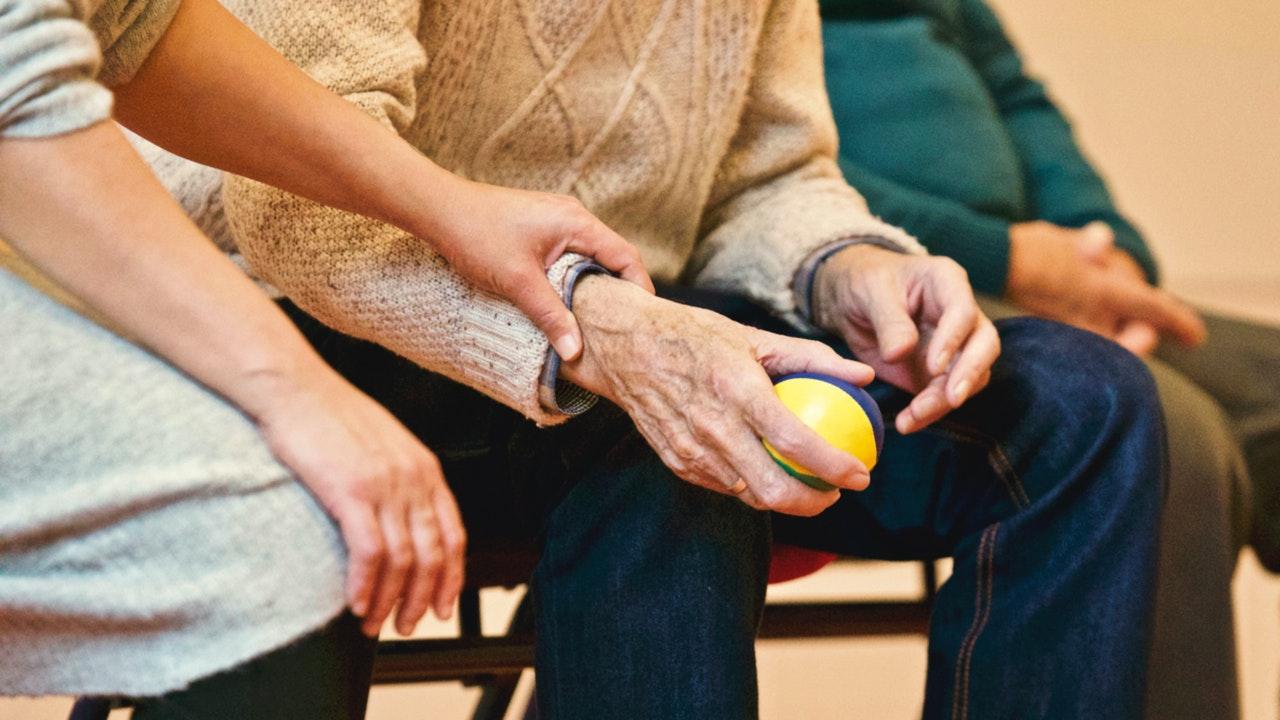 Care staff helping Parkinson's patient